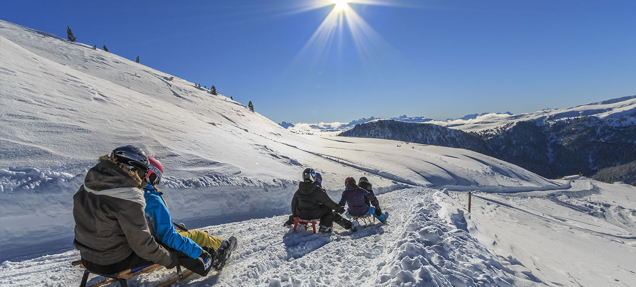People tobogganing in San Martino (Val Sarentino) in winter with snowy mountains at the back and beautiful sunshine