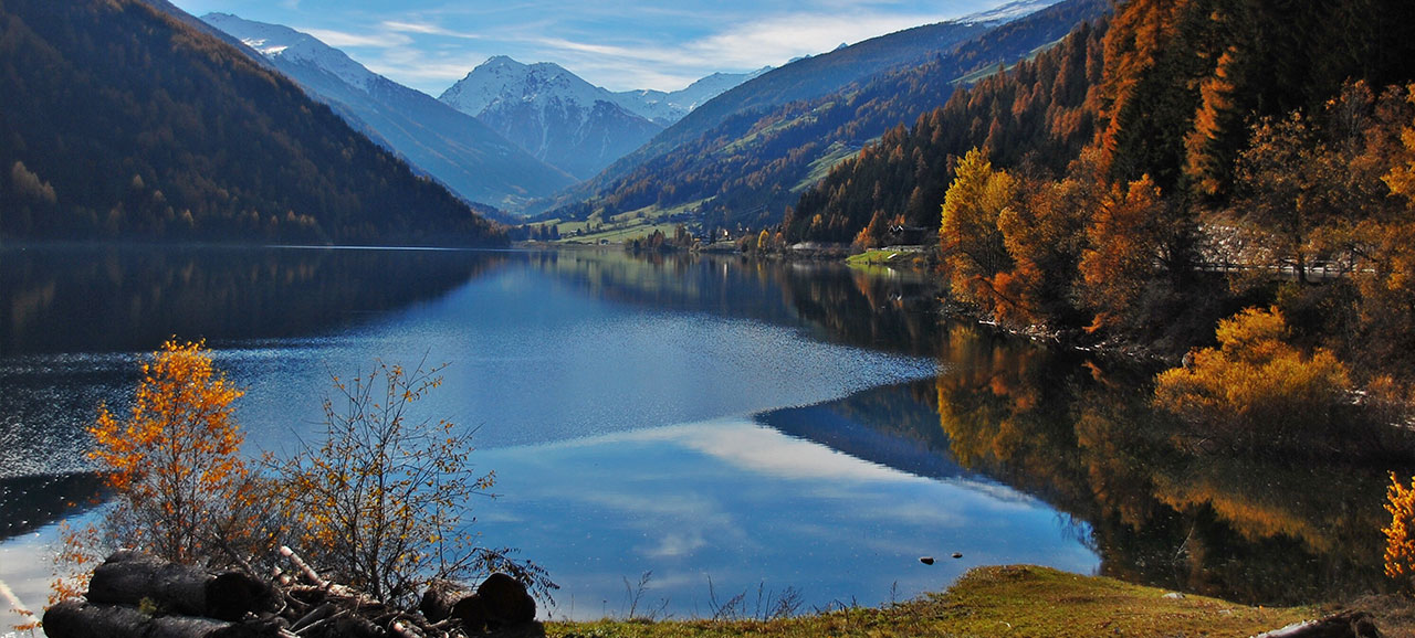 Lago di Zoccolo in autumn, surrounded by autumnal trees and with snowy mountains at the back