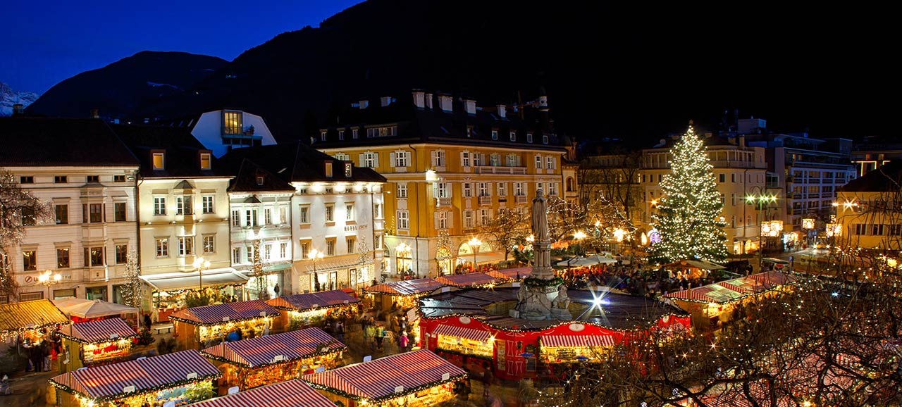 The Christmas market of Bolzano in the evening with all the illuminated stands and the glowing christmas tree