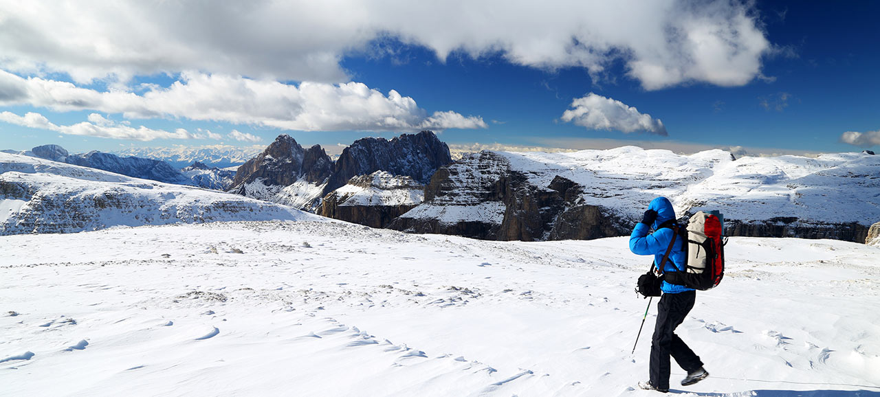 A mountain hiker with alpine equipment on the snowy peaks of the Dolomites