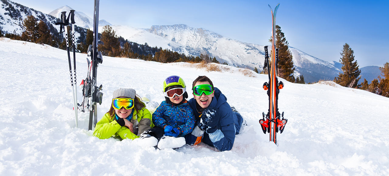 Family with skier equipment, helmets and goggles lying in the snow and smiling at the camera