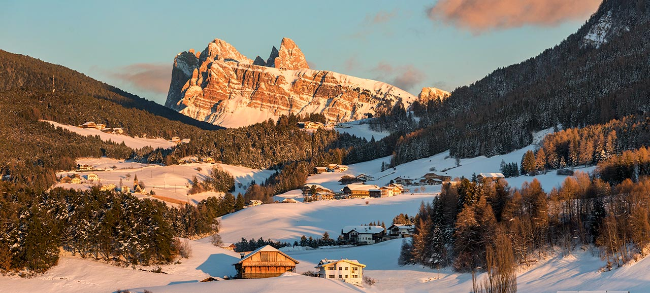 A panoramic image of the South Tyrolean snow-capped mountains at sunset
