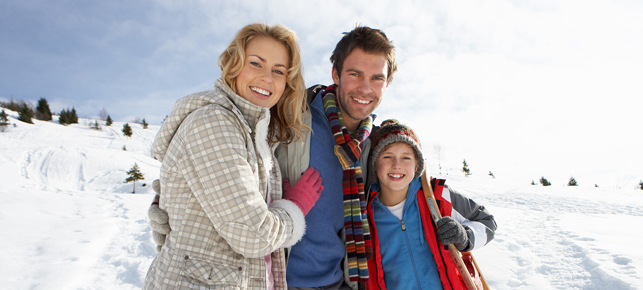 A smiling family of mother, father and son on a group photo in the middle of a snowy landscape