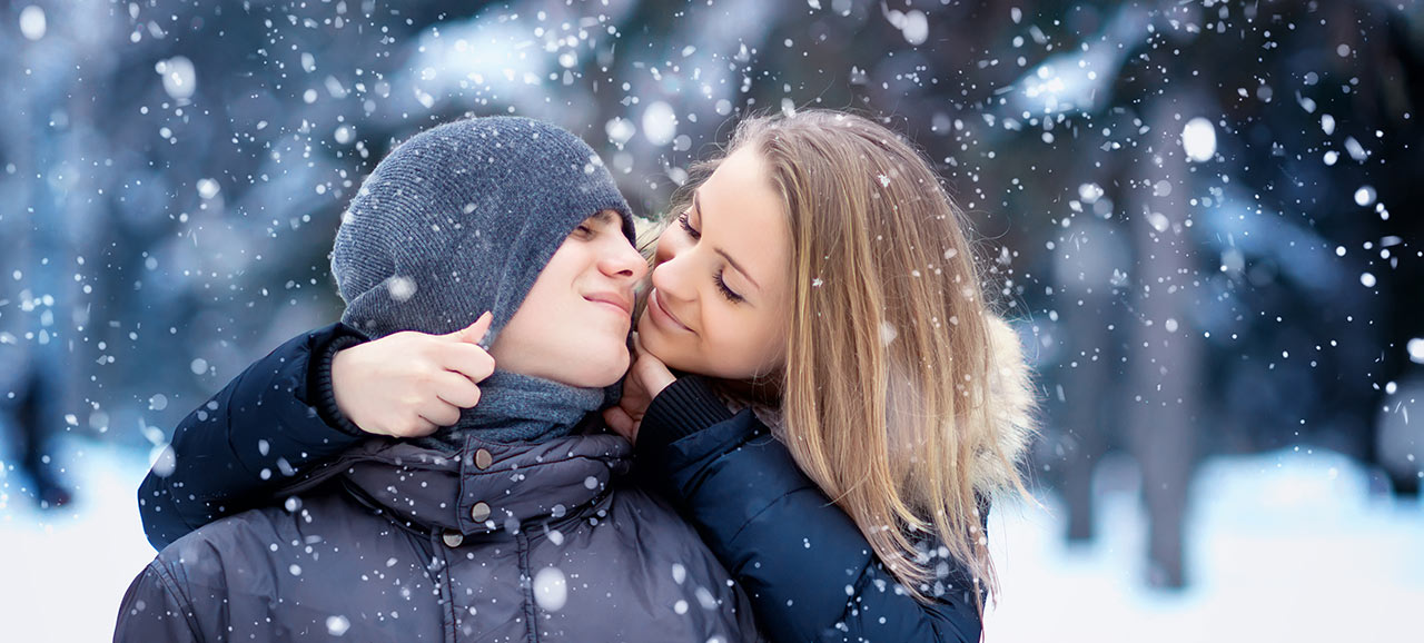 Courting couple in snow caress itself while it's snowing