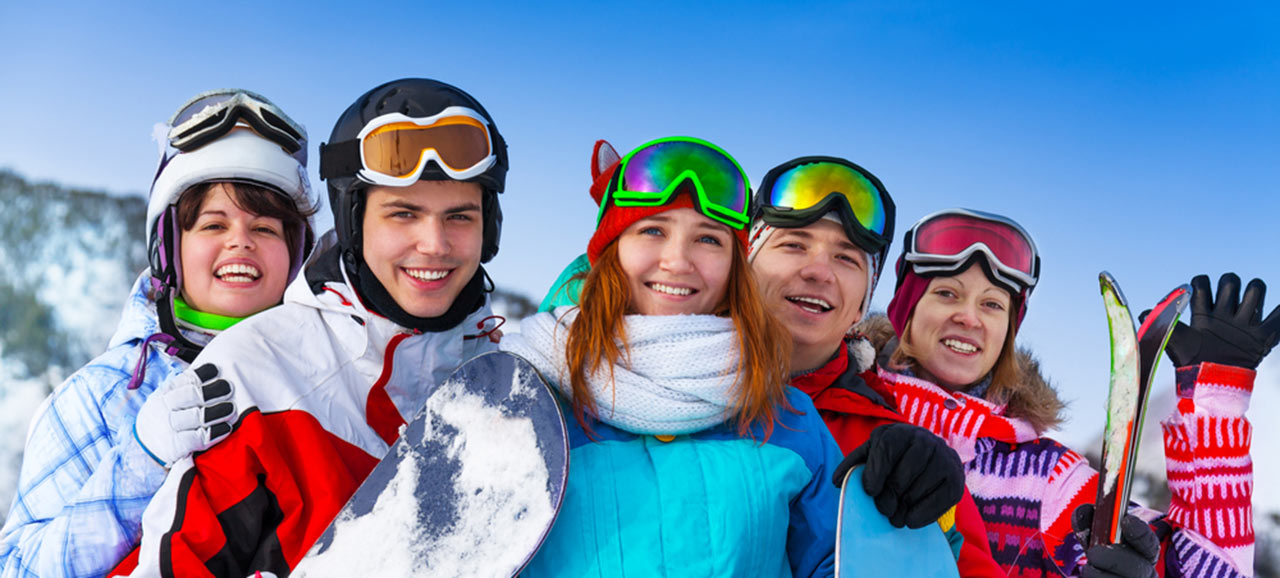Group photo of five friends with snowboards and skiersd on the slopes