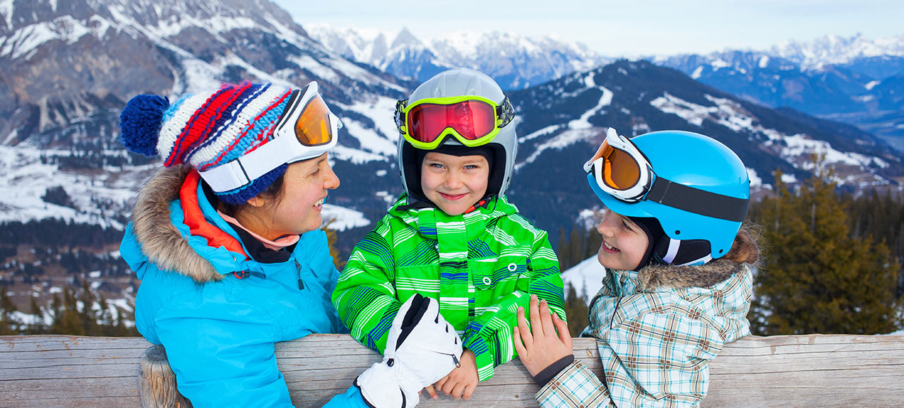 Mother and two children in full skiers equipment at a wooden fence smiling to each other